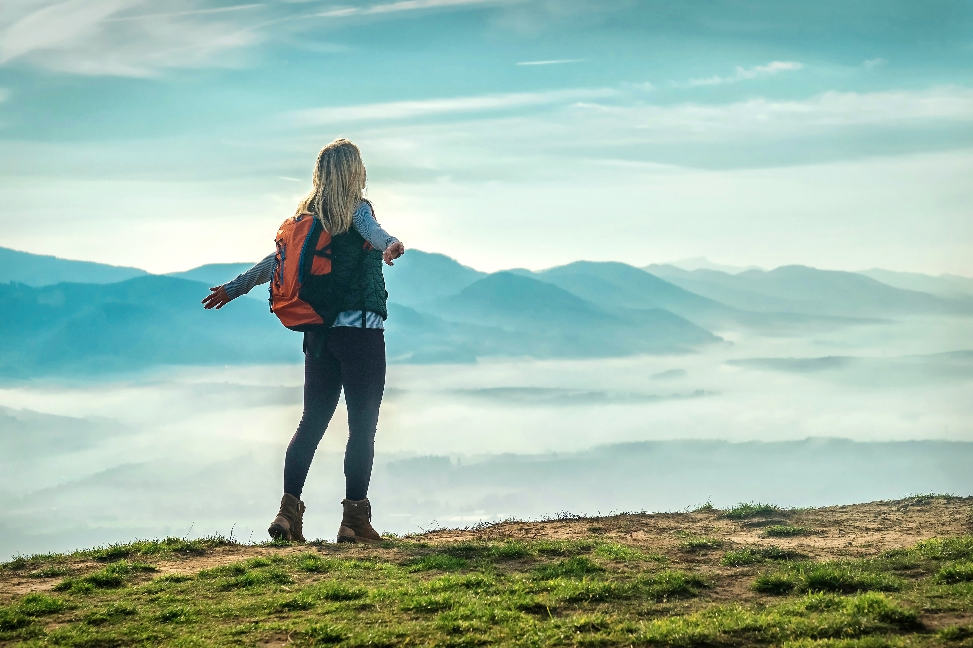 Happy woman tourist stay on the green grass on the peak of mountain and look on the nice fog view. Concept freedom.
