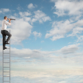 Businessman on a ladder high into the sky watching with binoculars